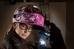 Woman wearing welding helmet