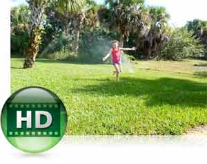 Nikon COOLPIX S3500 photo of a kid playing in a sprinkler in a garden to highlight HD video capability
