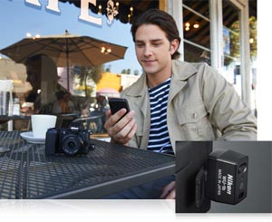 photo of a man at an outdoor cafe with his Nikon 1 V2 and smartphone