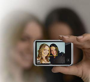 Photo of two women on the LCD of the COOLPIX S02 as one woman holds the camera
