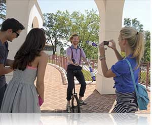 Photo of a woman and friends photographing a unicyclist with the COOLPIX S02