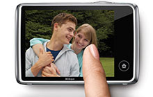 photo of a finger pointing to the image on the LCD of the COOLPIX S02, showing how simple the touchscreen is to use
