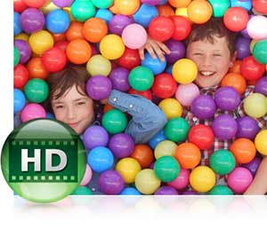 Nikon COOLPIX L30 photo of two boys in a ball pit and the HD video icon showing HD video capabilities.