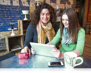 Photo of two women with smart devices and COOLPIX S6500 in coffee shop