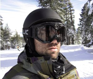 The image shows a snowboarder in a snowy forest wearing the All-Sport goggles.
